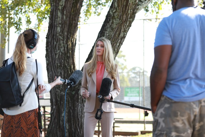 Loeffler speaks in front of a tree, wearing a beige pantsuit