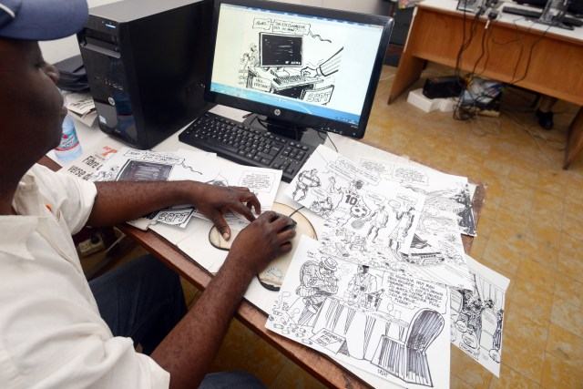 A man sits at a desk that's covered in hand drawn cartoons, touching one up on a computer screen in front of him.