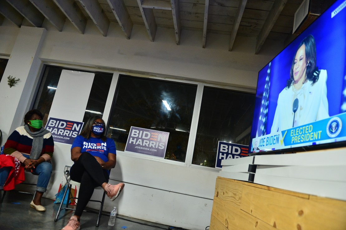 Two Black women wearing Biden/Harris shirts watch Harris, in white, speak on TV