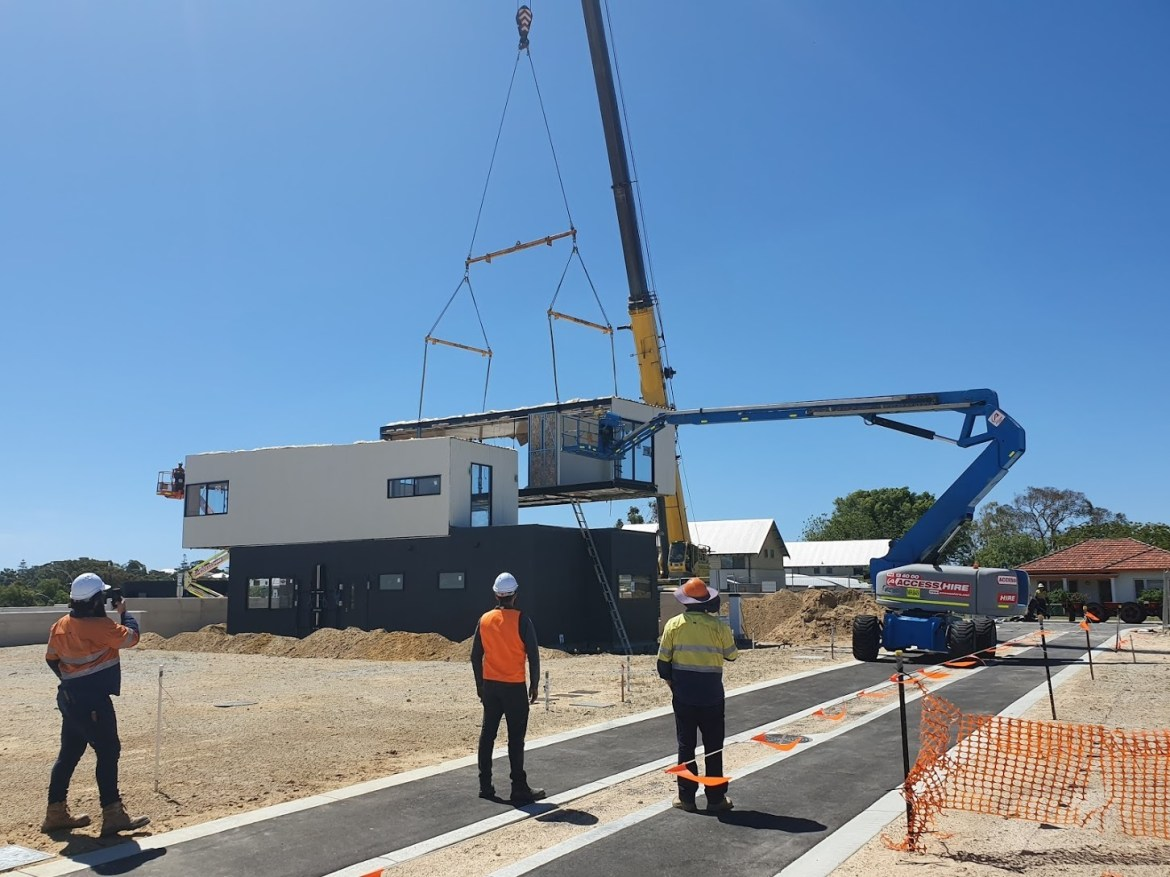 People watch as a crane lowers a building module into place