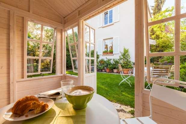 طاولة مع وجبة مطبوخة داخل غرفة مع الأبواب والنوافذ مفتوحة.