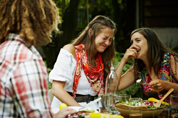 women laughing together at an outdoor meal