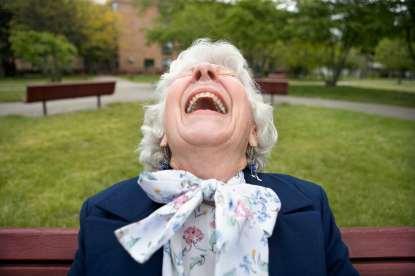 Femme aux cheveux blancs riant sur un banc public dans un parc