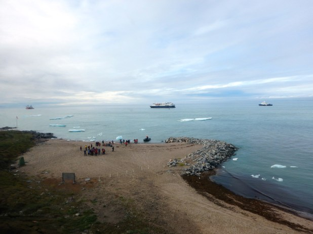 Ships anchored offshore in icy water with small group of passengers standing on a point of land.
