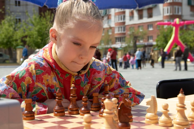 A girl plays chess in a public park.