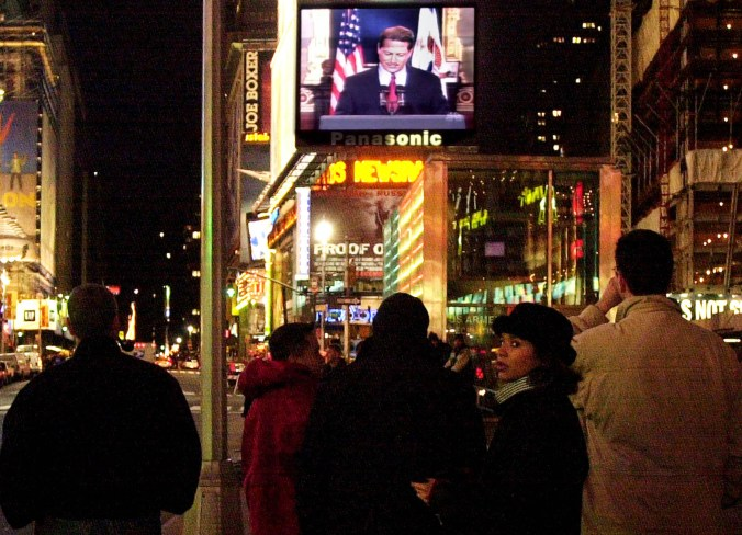 People in Times Square watch Vice President Al Gore concede the race for president to George W. Bush December 13, 2000 on a giant video screen in New York City.