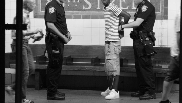 Black and whit image of police arresting a Black man in a New York subway station; no faces are seen