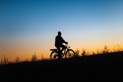 A silhouette of a person riding a e-bike against a sunset background.
