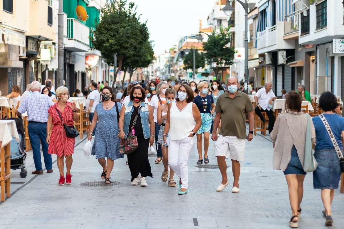People in masks walking down a street