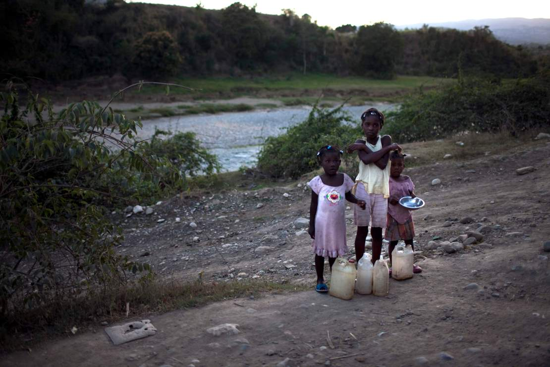 Three young girls stand on the side of a dirt rod in Haiti.