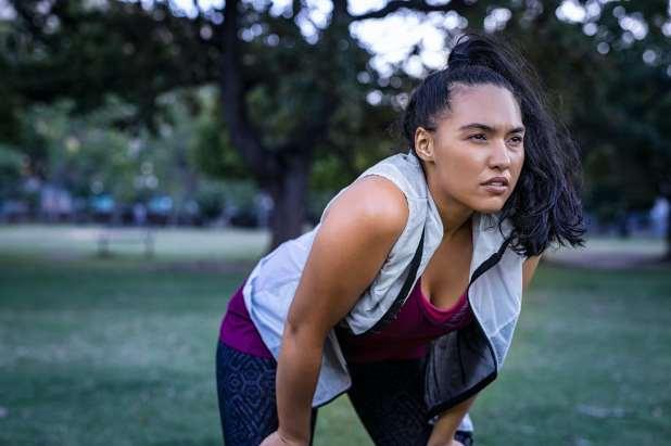 امرأة في الحديقة ترتدي ملابس رياضية تنحني للراحة