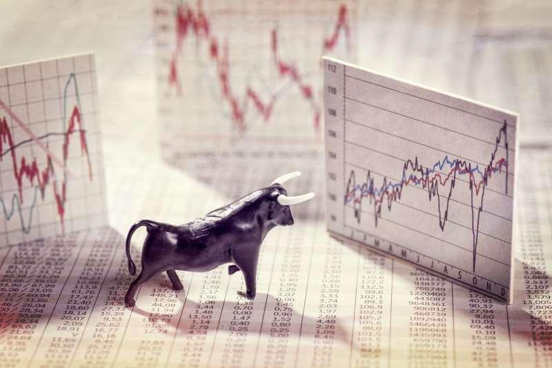 Small bull figurine among various printed charts.
