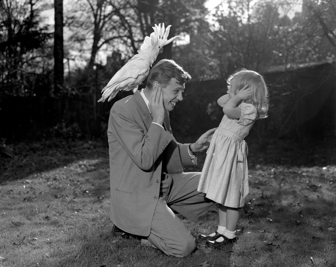 A man with bird on his back kneels beside his daughter.