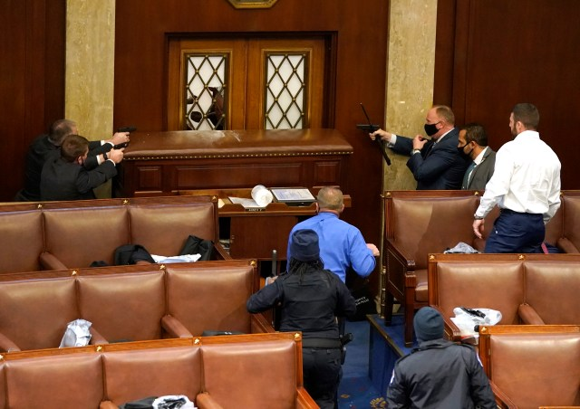 Capitol police officers point their guns at a vandalized door, barricaded to prevent entry.