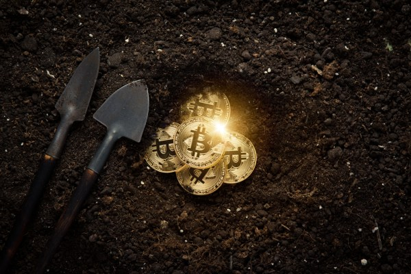 Graphic illustration of bitcoins being mined from a hole