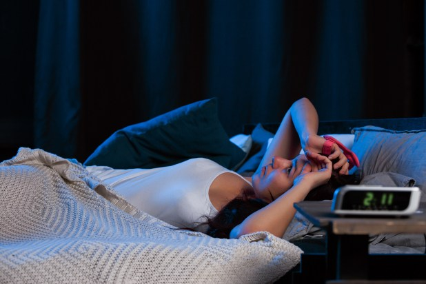 Woman with insomnia lying awake in bed, struggling to sleep.