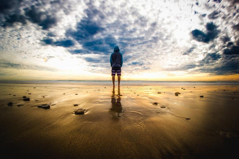 Man standing in front of sea with dramatic sky