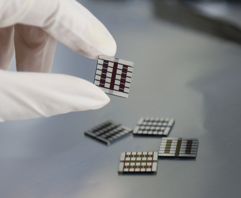 A gloved hand holds up a small solar cell.