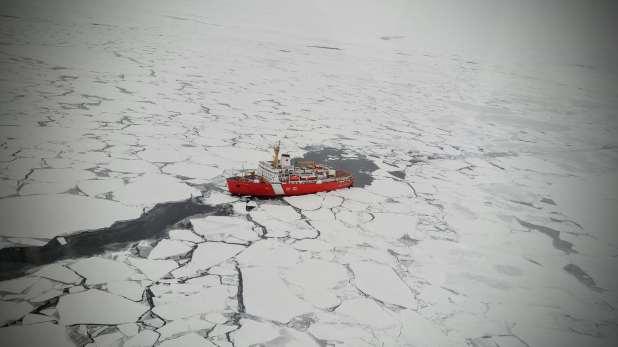 An icebreaker cuts a path through the ice floe in the Arctic Ocean.