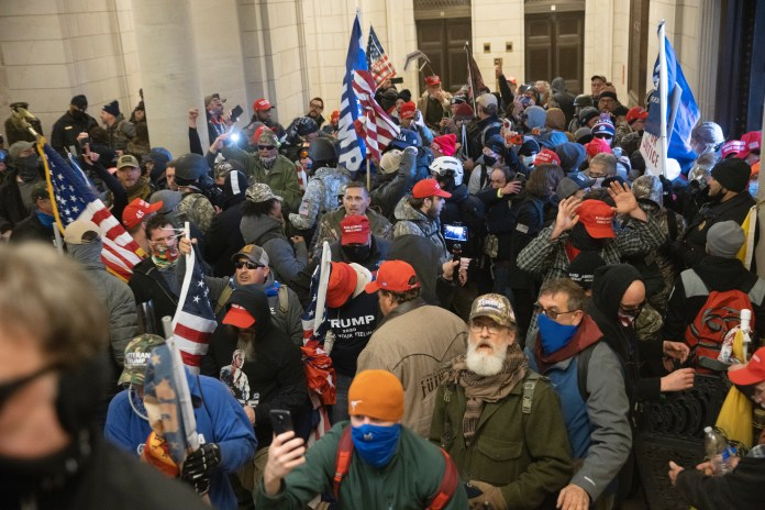 Pro-Trump protesters fill the U.S. Capitol building, many of them wearing military gear.