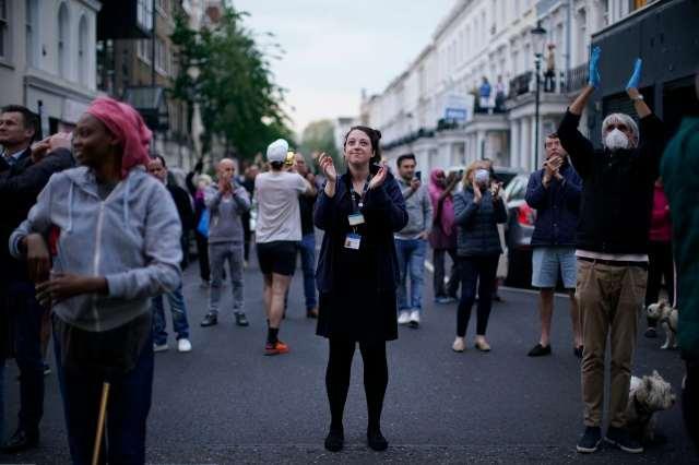 La gente se para en una calle de Londres y aplaude.