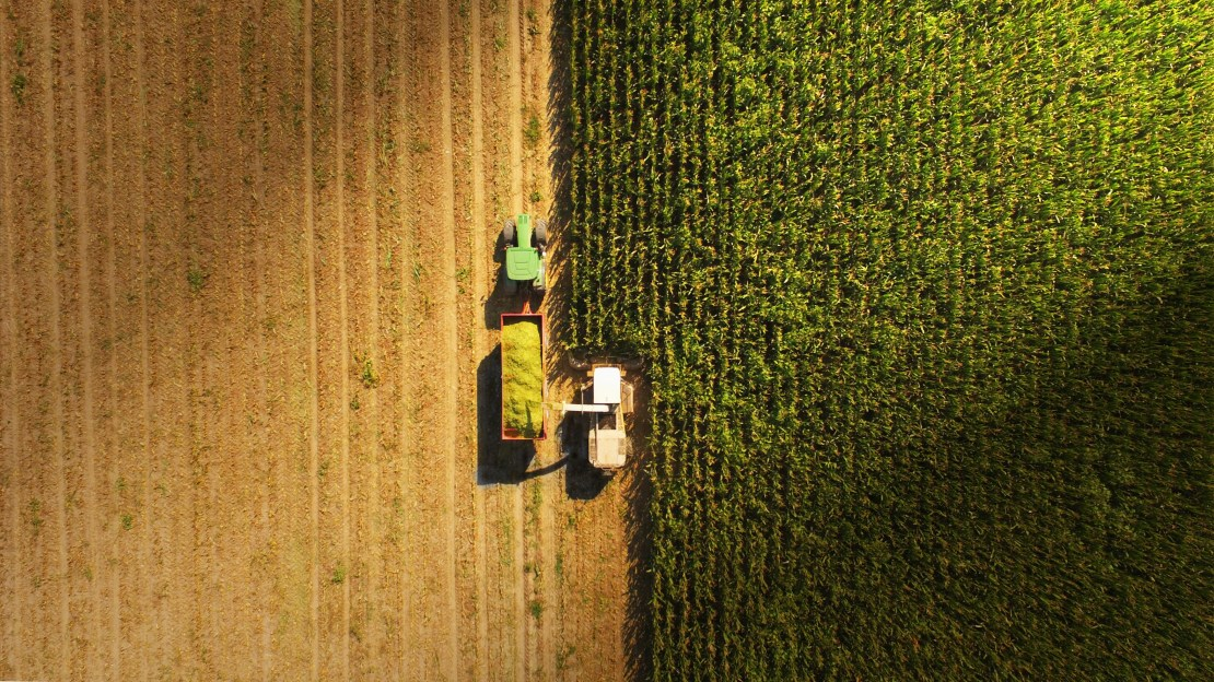 A tractor with wagon harvesting crops viewed from above