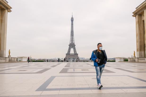 Man walking in front of deserted Eiffel Tower.