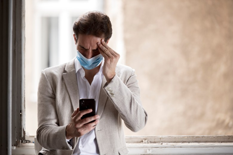 Man in medical face mask holds head and looks at phone in confusion