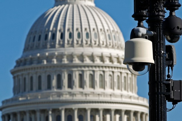 A security camera mounted on a streetlight pole with the U.S. Capitol dome in the background