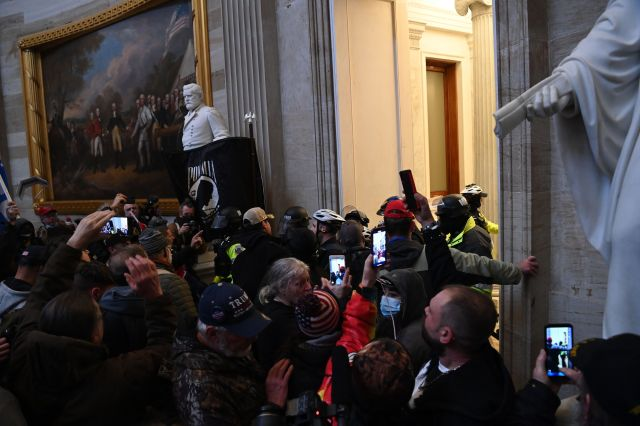 People crowded in the U.S. Capitol building rotunda using cell phones