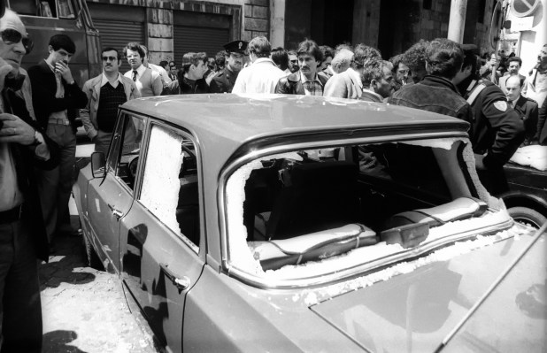 Black-and-white image of a crowd looking at a bullet-riddled car with shatters windshields and windows