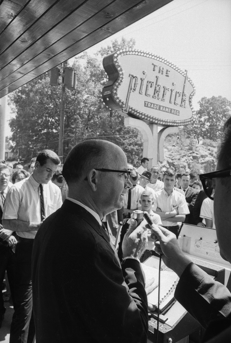 Black and white image of white man in glasses talking to press outside the Pickrick