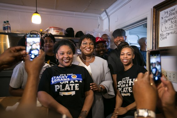 Abrams poses in a restaurant with other Black women, some wearing pro-Abrams gear