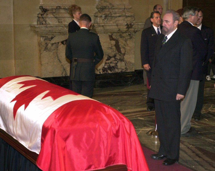 Fidel Castro looks at Pierre Trudeau's casket, draped with a Canadian flag.