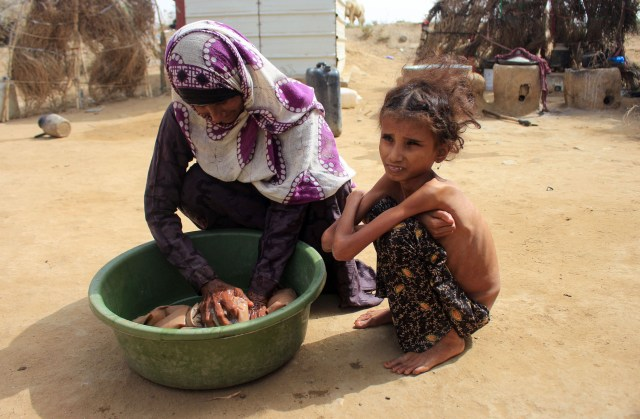 A extremely skinny 10-year-old child squats next to her mother, on the dirt ground
