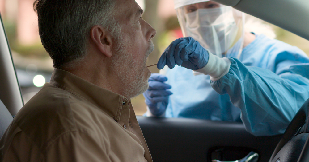 A man being a swab test while sitting in his car.