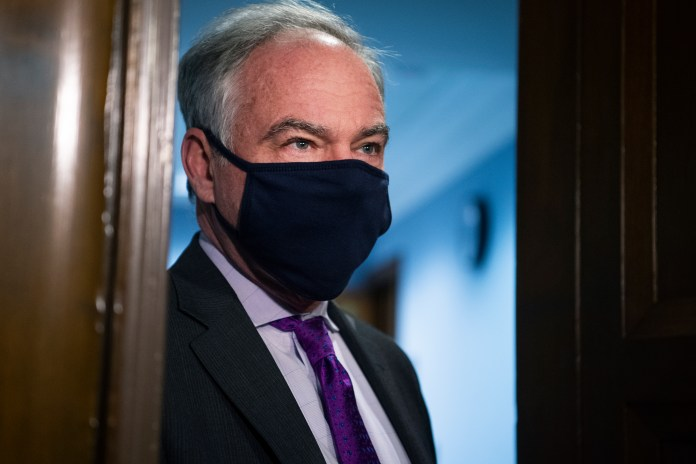 Kaine stands in a doorway wearing a face mask