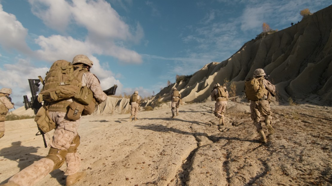 Squad of soldiers running with guns in a desert