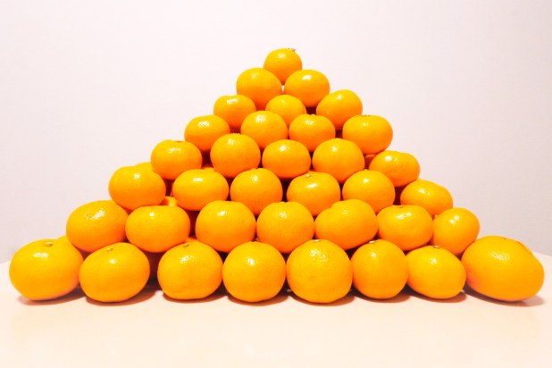 Oranges stacked up in a pyramid shape.
