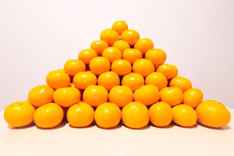 Naranjas apiladas en forma de pirámide.
