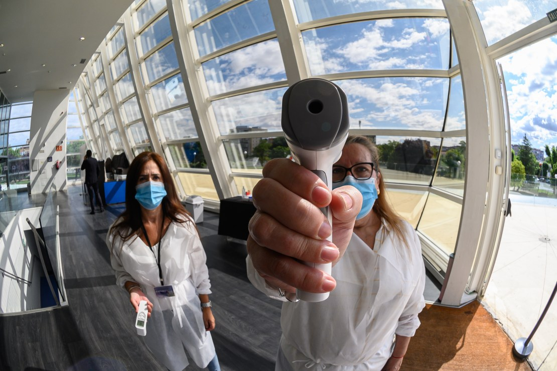 A woman holding an infrared scanner up to face the camera