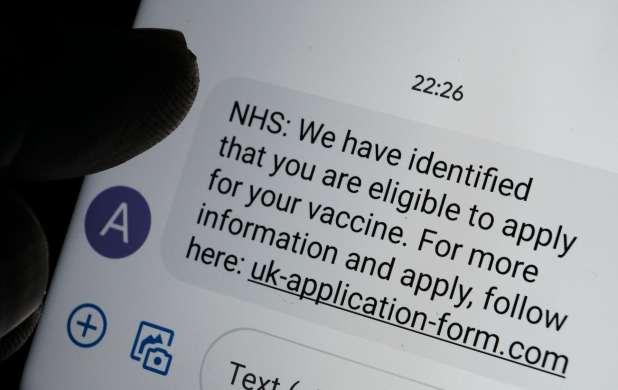 رسالة نصية احتيالية للقاح COVID-19 تظهر على شاشة الهاتف الذكي وصورة ظلية غير واضحة لإشارة الإصبع إليها.