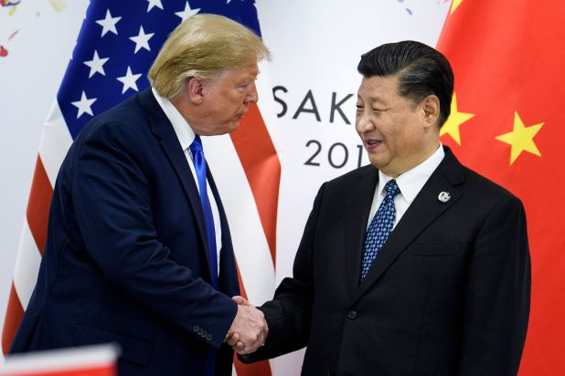 Trump and Xi shake hands in front of a Chinse and American flag