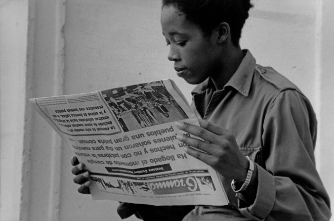 Black-and-white image of a young woman in fatigues reading the paper
