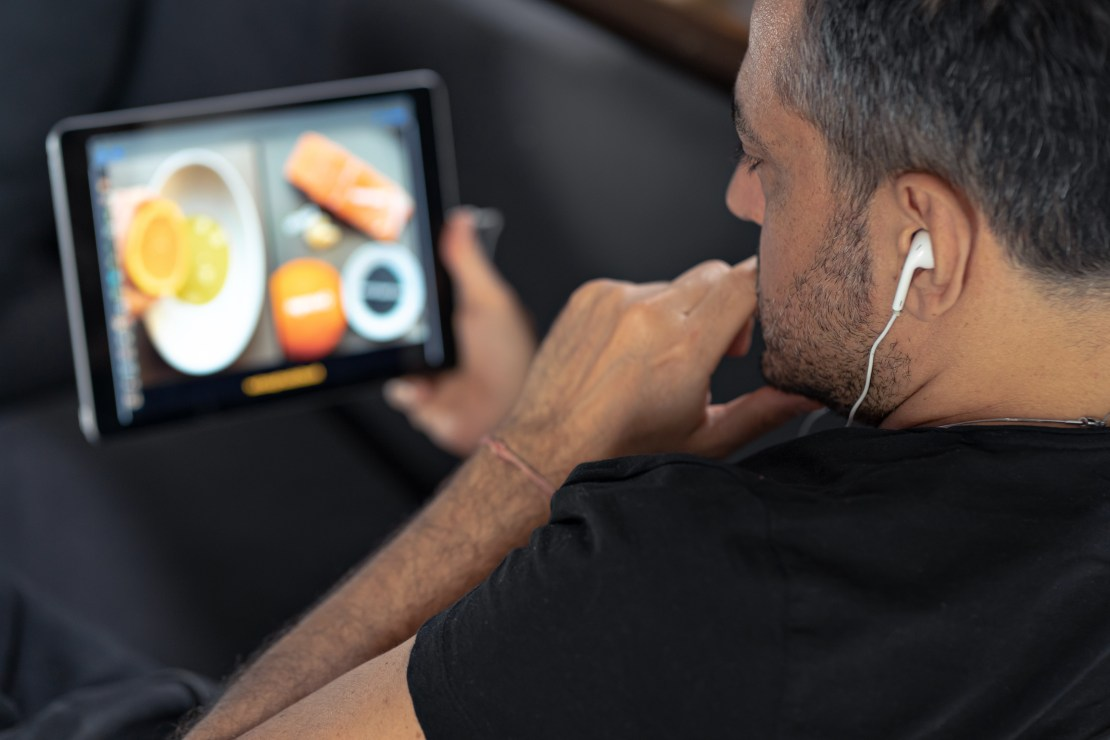 Man watches a cooking video on his tablet.