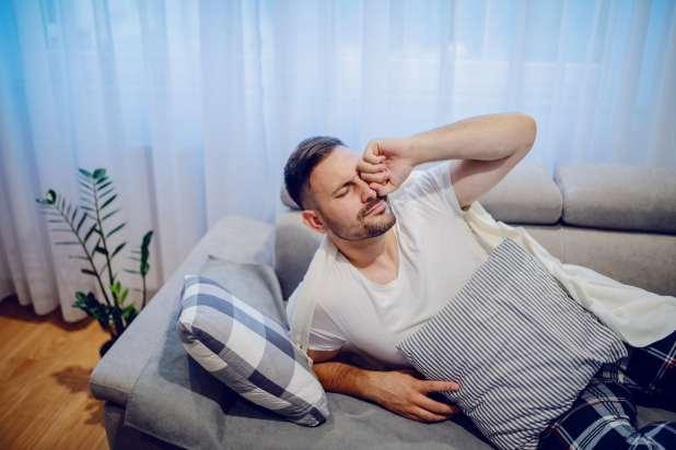 رجل يستيقظ من قيلولة على الأريكة