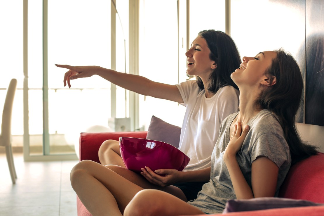 Image of two girls laughing in front of the TV.