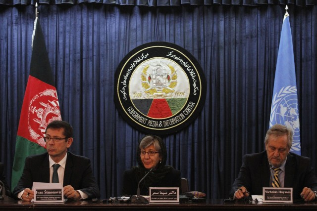 Woman in hijab sits at a table with microphones between two men in sits, with international flags behind them