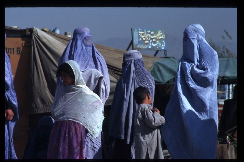 Veiled women and some children stand on the street