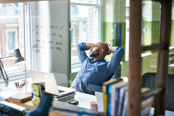 A man leans back from his desk